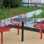 Korg fåtöljer i orange/röd och bord i svart, utearbetsplats i Växjö. Design Thomas Bernstrand